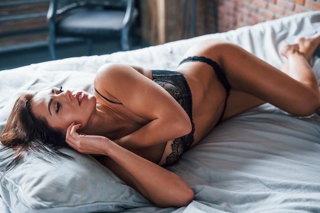 Belle femme brune sexy allongée sur le lit à l'heure du matin.