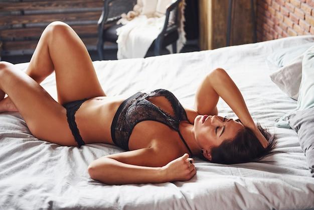 Belle femme brune sexy est sur le lit au moment du matin.
