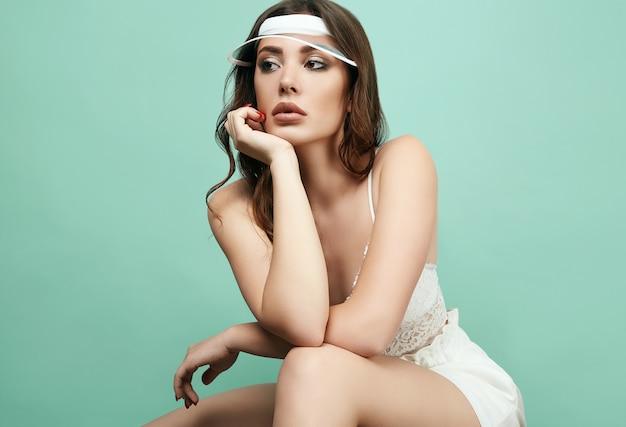 Belle femme brune sexy avec des lèvres juteuses en forme de sport blanc