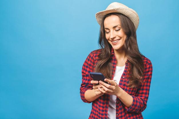 Belle femme brune souriante au chapeau de paille tenant un téléphone mobile envoi de message texte
