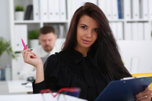 Belle femme brune souriante tenir dans les bras stylo rose