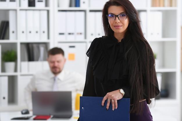 Belle femme brune souriante tient dans les bras un stylo rose et du papier coupé au pad portant des lunettes élégantes portrait.