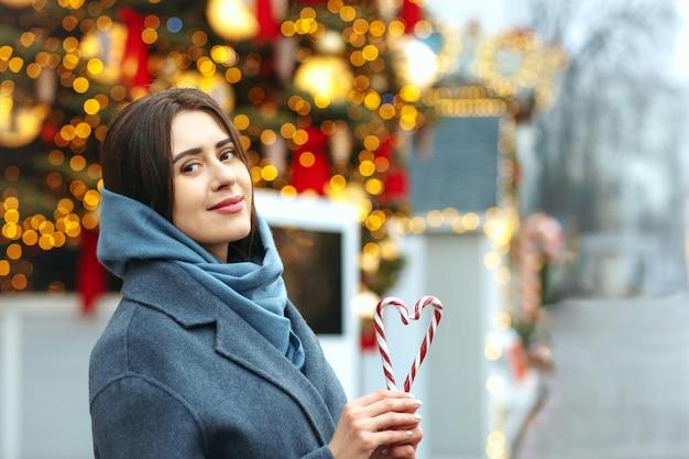 Belle femme brune tenant des bonbons en forme de coeur. espace pour le texte