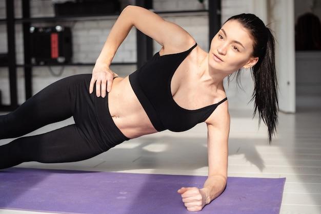 Belle femme brune en vêtements de sport ayant une séance d'entraînement active sur un tapis de yoga. jeune femme faisant des exercices de fitness à la maison.