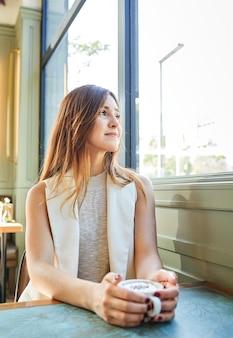 Belle femme buvant un café dans un bar