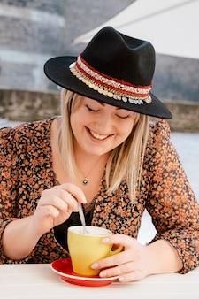 Belle femme buvant un café à l'extérieur sur une terrasse ensoleillée