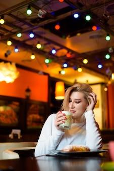 Belle femme buvant du café au café en hiver.