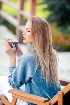 Belle femme buvant du café en automne parc sous le feuillage d'automne