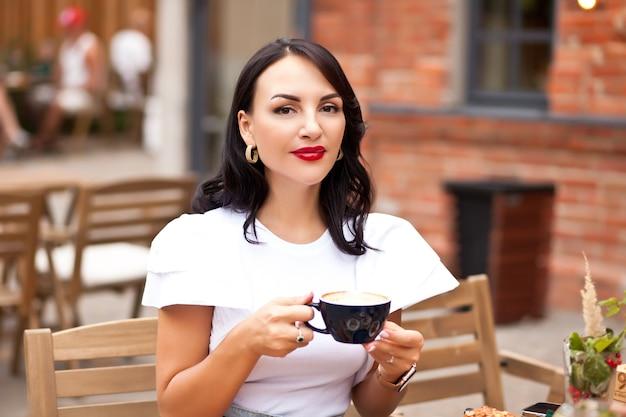Belle femme buvant du café dans un café
