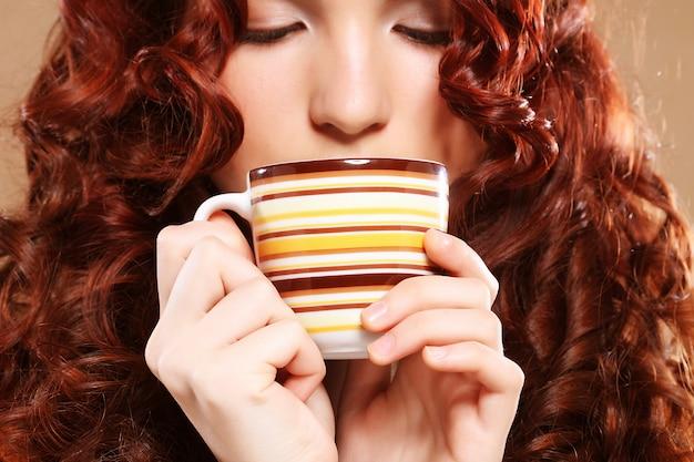 Belle femme buvant du café sur fond beige