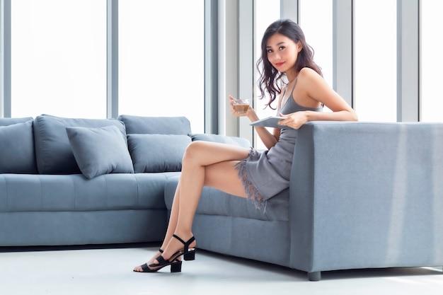 Belle femme buvant du café et shopping en ligne avec tablette dans le salon.