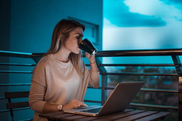 Belle femme buvant du café le soir tout en utilisant un ordinateur portable. image iso élevée.