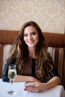 Belle femme buvant du champagne et parler au téléphone dans le restaurant