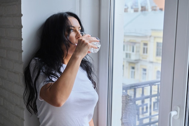 Belle femme buvant du lait, du yaourt en verre