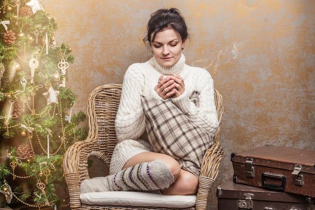 Belle femme buvant du thé ou du café assis sur une chaise avec des oreillers à l'intérieur de noël