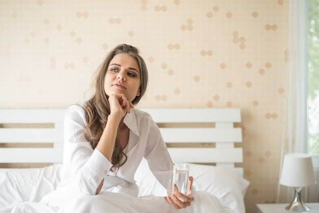 Belle femme buvant de l'eau fraîche dans le lit le matin
