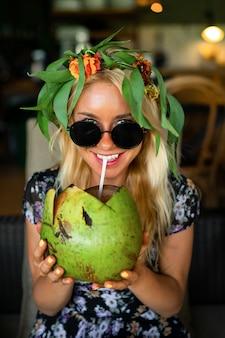 Belle femme buvant de la noix de coco dans le café tropical