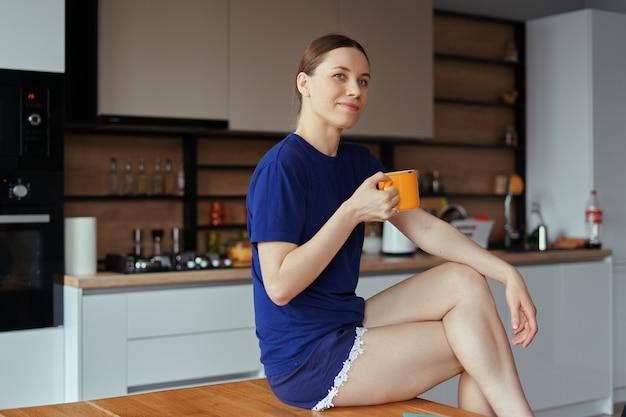 Belle femme buvant une tasse de thé dans la cuisine