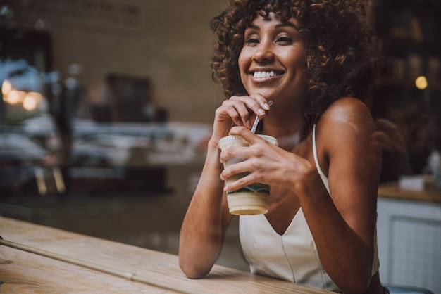 Belle femme buvant un verre à l'intérieur d'un café, vue à travers l'écran