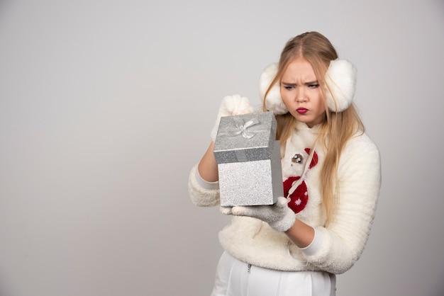 Belle femme en cache-oreille blanc regardant à l'intérieur de la boîte-cadeau.