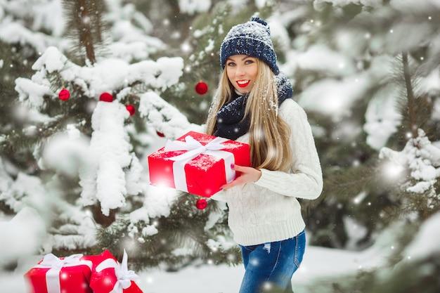 Belle femme avec des cadeaux de noël sur une scène d'hiver avec des arbres enneigés