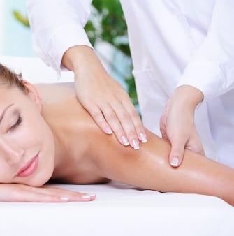 Belle femme calme se massage de l'épaule dans le salon de beauté