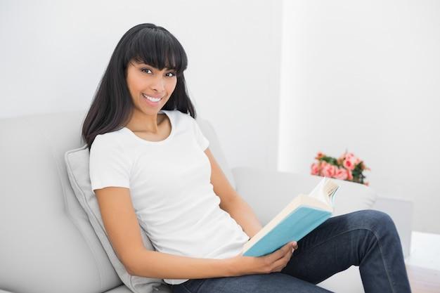 Belle femme calme, tenant un livre assis sur un canapé