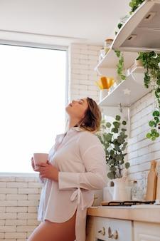 Belle femme calme tenant une tasse de thé tout en se relaxant à la maison pendant le week-end