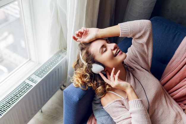 Belle femme sur le canapé, écouter de la musique