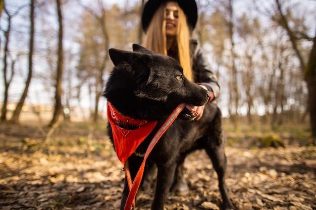 Belle femme caresse son chien en plein air