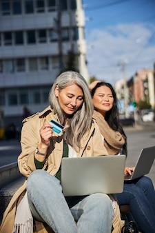Belle femme avec carte de crédit à l'aide d'un ordinateur portable dans la rue