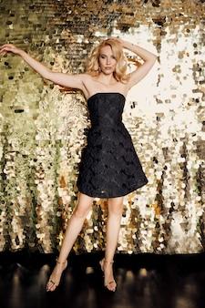 Belle femme caucasienne blonde en petite robe noire sur la fête sur fond doré