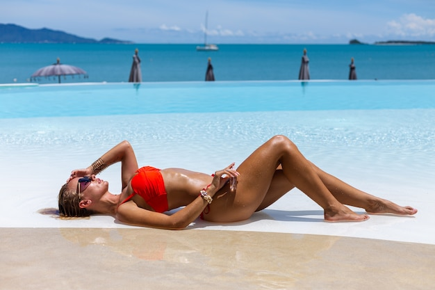 Belle femme caucasienne bronzée, peau brillante de bronze en bikini avec de l'huile de noix de coco