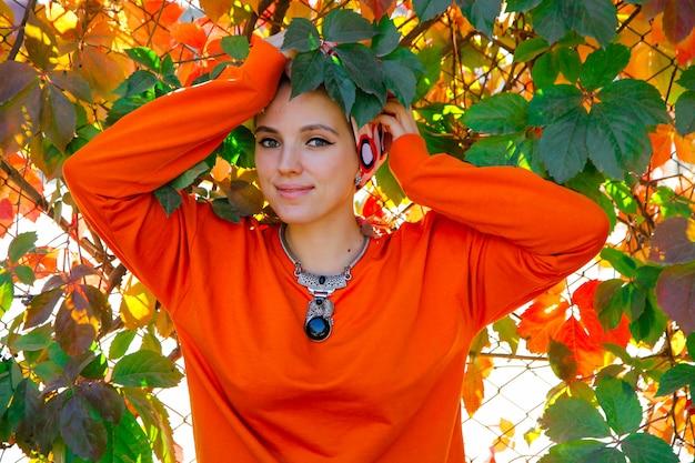 Belle femme caucasienne à capuche orange parmi les feuilles colorées de l'automne. gens dans le concept de temps d'automne.