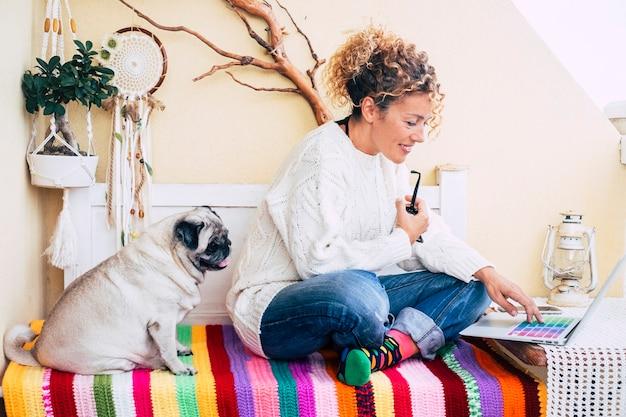 Belle femme caucasienne et drôle de vieux chien carlin assis sur un banc sur la terrasse à la maison travaillant ou faisant des achats en ligne avec un ordinateur portable ensemble