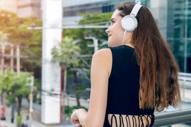 Belle femme caucasienne, écouter de la musique avec des écouteurs dans la ville.