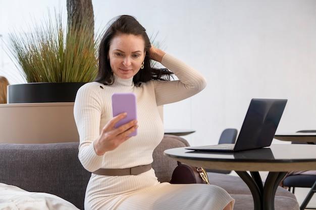 Belle femme caucasienne fait selfie sur un smartphone assis à une table avec un ordinateur portable un blogueur