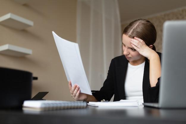 Belle femme caucasienne lit un document et exprime un malentendu. travail à distance de la maison.
