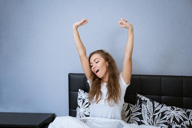 Belle femme caucasienne à la maison au lit se détendre sourire heureux femme brune beau modèle vie décontractée...
