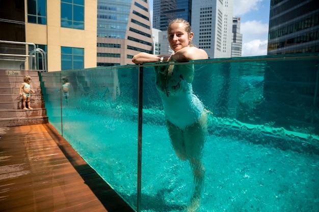 Belle femme caucasienne se reposant dans la piscine avec mur de verre sur fond de paysage urbain