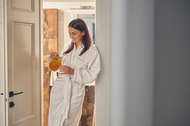 Belle femme caucasienne souriante versant de la limonade dans un verre dans la salle blanche