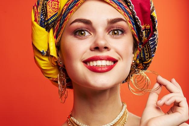 Belle femme châle multicolore ethnique style africain fond rouge. photo de haute qualité