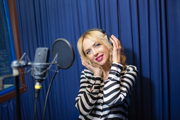 Belle femme chantant dans un studio d'enregistrement