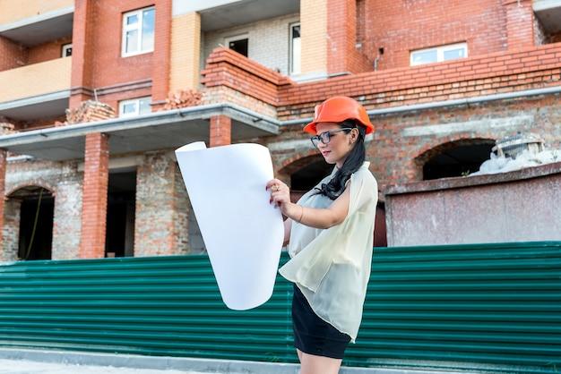Belle femme sur chantier à la recherche de plan directeur