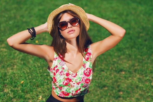 Belle femme avec chapeau posant sur l'herbe