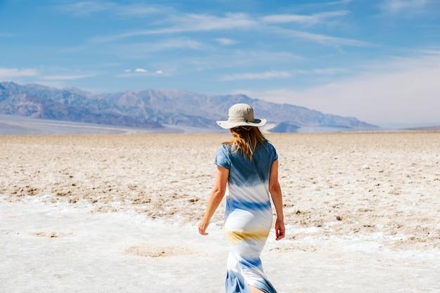 Une belle femme avec un chapeau et une robe d'été en promenades bleues blanches et jaunes exécute des sauts et profite du paysage désertique de death valley en californie usa