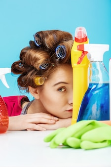 Belle femme charmante se cache derrière la bouteille et les outils de nettoyage
