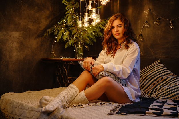 Une belle femme en chemise blanche d'homme sur le lit