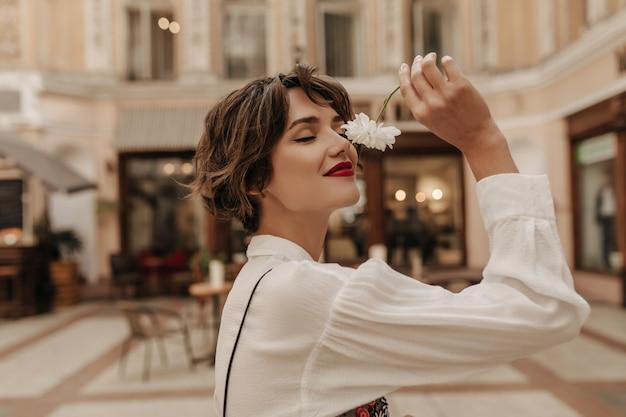 Belle femme en chemise blanche à manches longues tenant une fleur en ville. femme aux cheveux courts avec rouge à lèvres posant dans la rue.