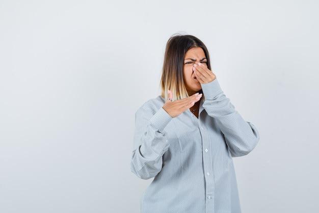 Belle femme en chemise pinçant le nez à cause d'une mauvaise odeur et ayant l'air dégoûtée, vue de face.